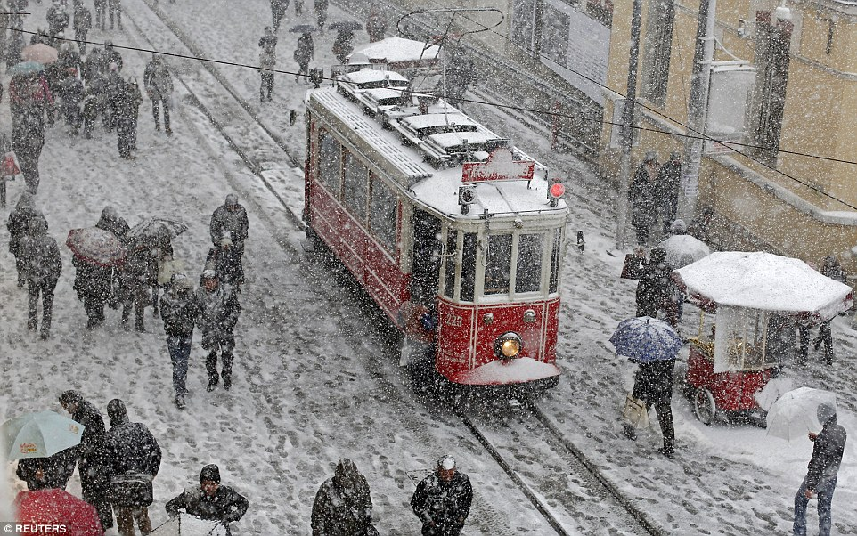 Omenii înfruntă frigul și zăpada pe strada Istiklal în centrul Istanbulului. Autor: